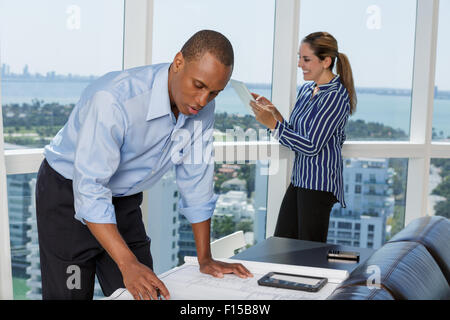 Male architect working on blueprint and his female colleague using digital tablet - Stock Photo