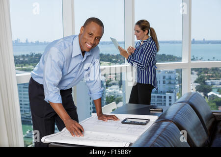 Happy male architect working with his female colleague using digital tablet - Stock Photo