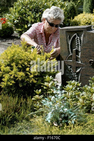 Woman maintains a grave - Stock Photo