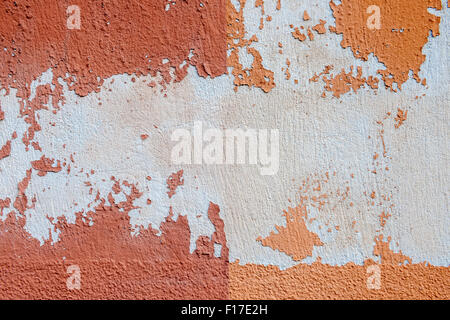 Abstract background of old vintage painted plastered wall with peeling paint and plaster texture in red orange colors - Stock Photo