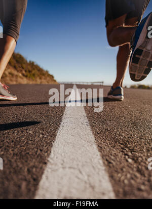 Low angle shot of runners legs running on middle of the road. Rear view close-up image of man and woman jogging - Stock Photo