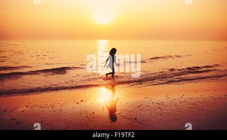 Child running beach during sunset - Stock Photo