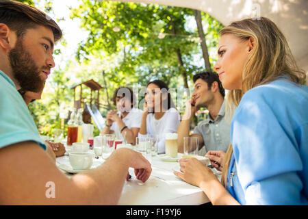 Group of a happy friends sitting at the table in outdoor restaurant - Stock Photo