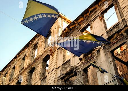 Ruins of Bosnia's Civil War and Bosnian flags in Mostar. - Stock Photo