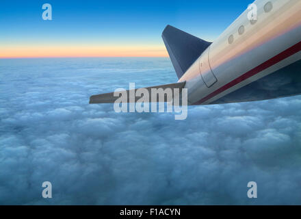 Commercial Airline Jet Airplane Flying Above Clouds At Sunset - Stock Photo