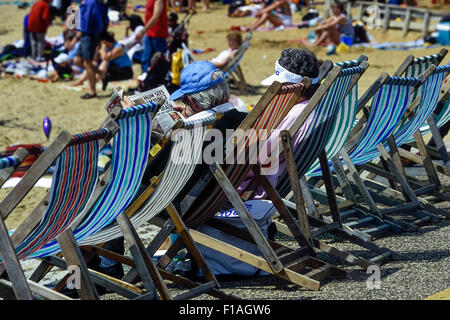 Holiday makers sitting in deck chairs. Southend-on-Sea. Essex. UK - Stock Photo