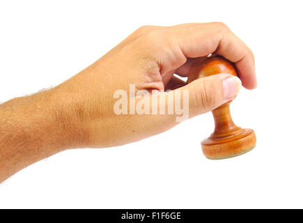 Hand stamping with an old and vintage wooden stamper isolated on white background - Stock Photo