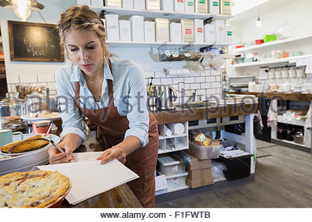 Tea shop owner doing paperwork at counter - Stock Photo
