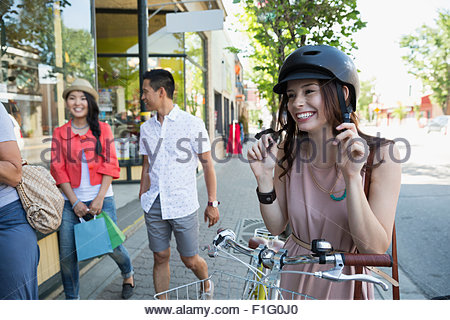 Smiling woman with bicycle putting on helmet - Stock Photo