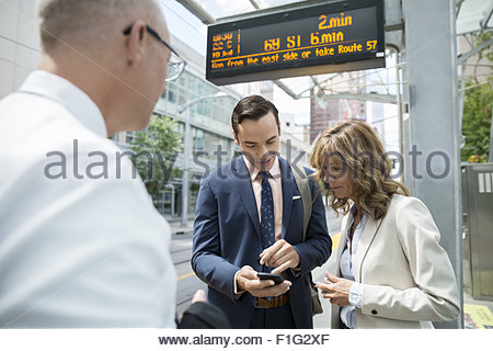 Business people looking down cell phone train station - Stock Photo