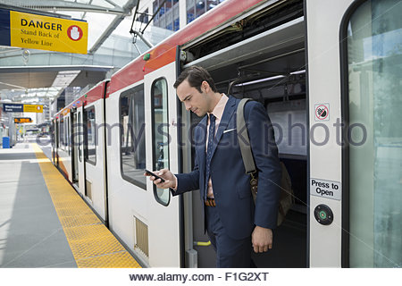 Businessman disembarking train texting with cell phone - Stock Photo