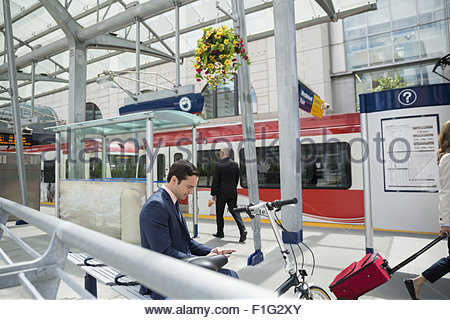 Businessman texting with cell phone at trains station - Stock Photo