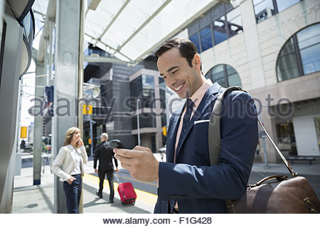 Smiling businessman checking cell phone at train station - Stock Photo