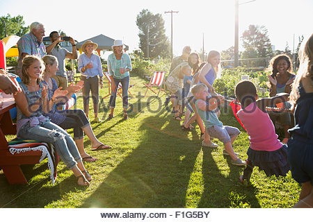 Neighbors cheering kids playing tug-of-war - Stock Photo