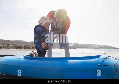 Father helping son adjust lifejacket in canoe, Loch Eishort, Isle of Skye, Hebrides, Scotland - Stock Photo