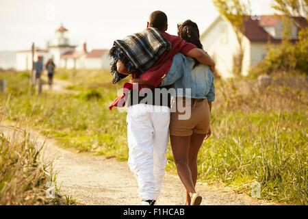 Rear view of young couple strolling with arms around each other - Stock Photo