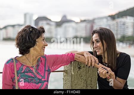 Mature woman holding hand of her mother at beach, Copacabana, Rio de Janeiro, Brazil - Stock Photo
