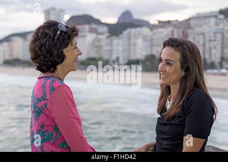 Portrait of mature woman and mother face to face at beach, Copacabana, Rio de Janeiro, Brazil - Stock Photo