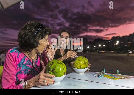 Mature woman and mother drinking from coconut shells at beach at night, Copacabana, Rio de Janeiro, Brazil - Stock Photo