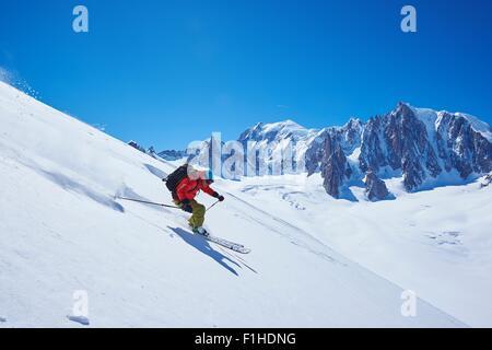 Male skier speeding downhill,  Mont Blanc massif, Graian Alps, France - Stock Photo