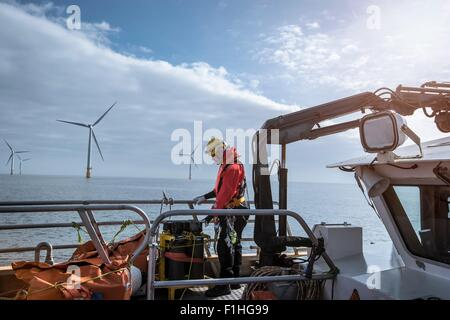 Engineer on deck of service boat at offshore windfarm - Stock Photo