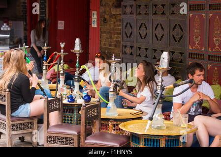 London , Camden Market , young boys & girls smoking at hookah shisha waterpipe narghile arghile qalyan bar cafe - Stock Photo