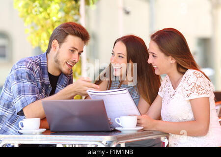 Three students studying and learning in a coffee shop with a laptop and notes - Stock Photo