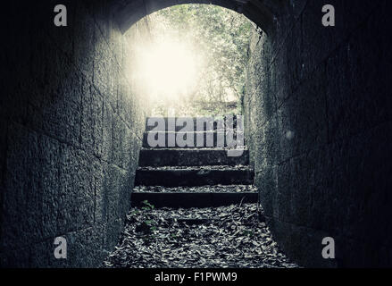 Glowing exit with stairs and lens flare from dark abandoned concrete tunnel interior, tonal correction filter - Stock Photo