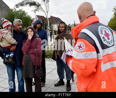 Eisenhuettenstadt, Germany. 7th Sep, 2015. A staff of the German Red Cross (R) guides arriving refugees to the medical - Stock Photo