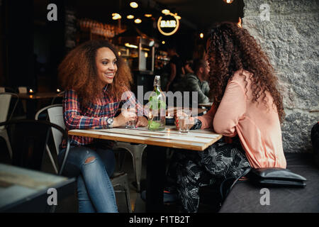 Two young women talking sitting in a restaurant. African woman smiling and chatting with her friend in a cafe. - Stock Photo