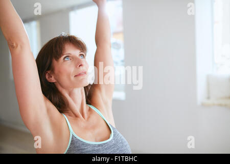 Close up shot of mature woman practicing yoga with her arms raised and looking upwards at gym. Fitness female in - Stock Photo