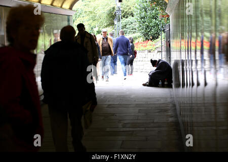 A homeless male sat begging but looking down and out in an underpass in central London as people pass by on a busy - Stock Photo