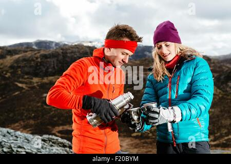 Young couple taking a break from hiking, having hot drink, Honister Slate Mine, Keswick, Lake District, Cumbria, - Stock Photo