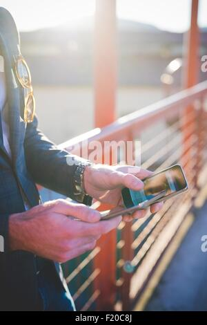 Cropped close up of young mans hands using digital tablet and smartphone on footbridge - Stock Photo