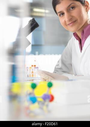 Portrait of female scientist testing blood sample using microscope - Stock Photo