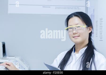 Portrait of female scientist with digital tablet in laboratory - Stock Photo
