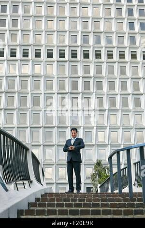 Low angle view of business man standing at top of stairway looking at watch - Stock Photo