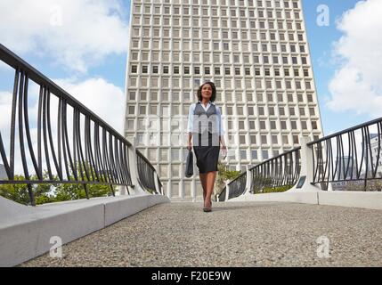 Low angle view of business woman carrying briefcase - Stock Photo