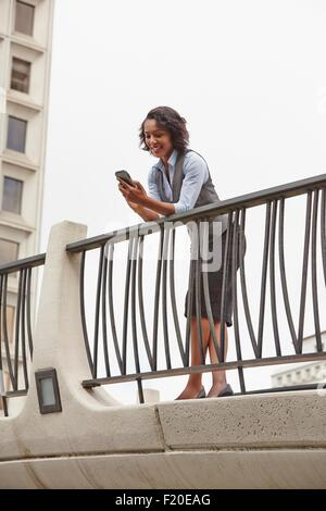 Young business woman leaning forward against railings looking at smartphone, smiling - Stock Photo