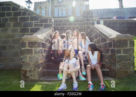 Group of students taking break on steps - Stock Photo