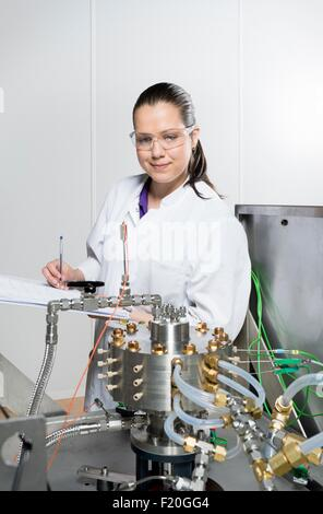 Portrait of female scientist, doing research on a innovative technology for mixing chemicals, at a hightech startup - Stock Photo
