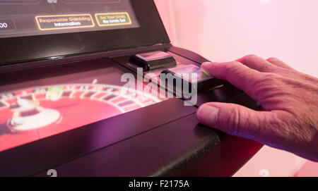 Man playing on fixed odds roulette machine in Bookmakers. UK - Stock Photo