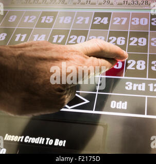 Man with fingers crossed playing on fixed odds roulette machine in Bookmakers. UK - Stock Photo