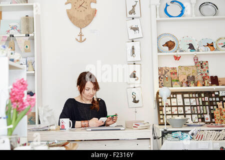 A woman sitting at a desk in a small gift shop, doing the paperwork, managing the business, using a laptop and a - Stock Photo