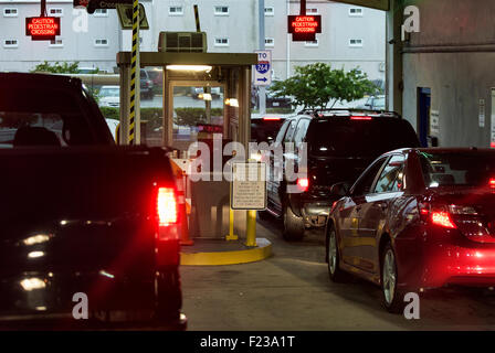 Cars wait to pay fee at a parking garage exit. - Stock Photo