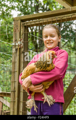 Eleven-year old girl holding an Ameraucana hen in front of a chicken coop in Issaquah, Washington, USA - Stock Photo