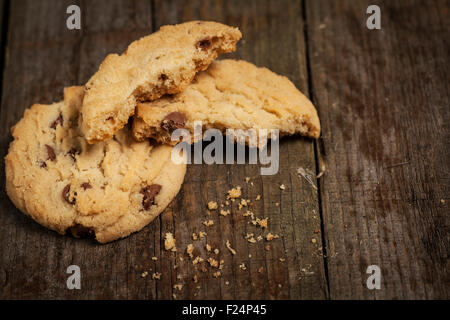 Chewy chocolate chip cookies on a wooden table sat on hessian - Stock Photo