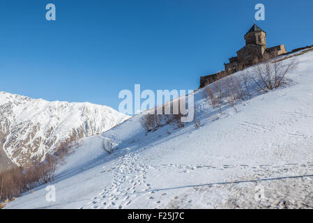 Famous 14th century Holy Trinity Church (Tsminda Sameba) near Gergeti village, Stepantsminda town and Mount Kazbek - Stock Photo