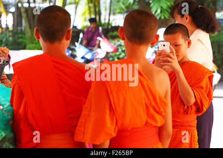 Vientiane, Laos. 12th September 2015. A young monk takes a photo of his friends at Wat Inpeng Temple during Boun - Stock Photo