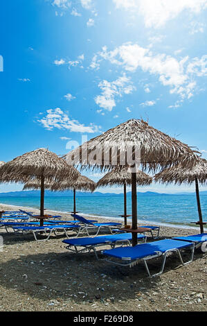 Beach with empty sunbeds and parasols on Pelion Peninsula, Thessaly, Greece - Stock Photo